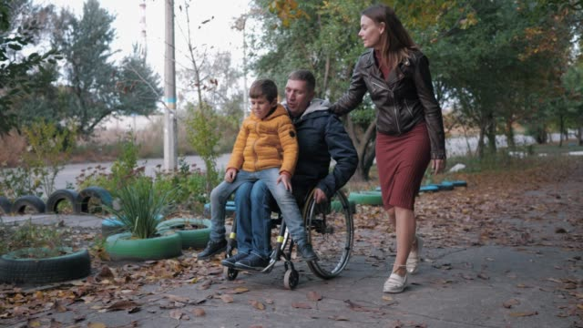 vídeos de stock e filmes b-roll de family walk, disabled father in a wheelchair carries his son on his knees walking in autumn street with his smiling wife - pessoas com deficiência