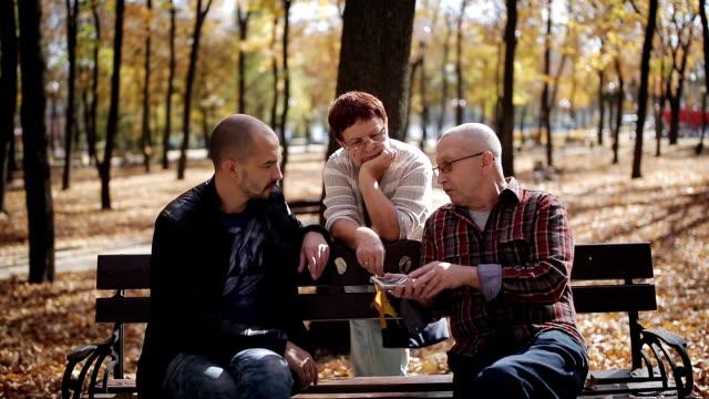 家族は公園を歩きます。世代間のリンク。秋の公園で高齢の両親と話して大人の息子。 - ベンチ点の映像素材/bロール