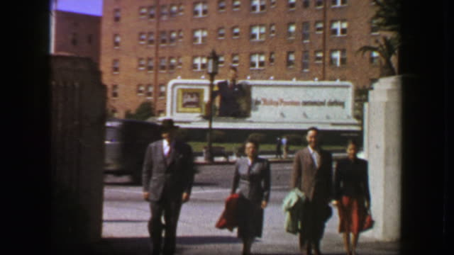 1957: Family walking 50s style advertisement billboard background. video
