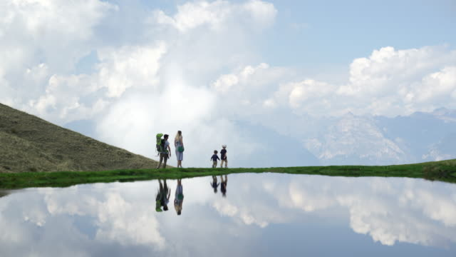 알파인 호수, 구름과 거리에서 산의 보기를 따라 산책 하는 가족 - mountain top 스톡 비디오 및 b-롤 화면