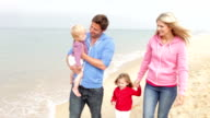istock Family Walking Along Beach Together 163089723