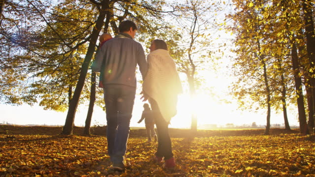 SLO MO Family walking in autumn park