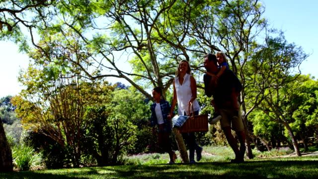 晴れた日 4 k にピクニックのための公園の歩行の家族 ビデオ