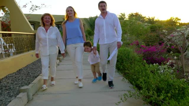 семьи ходьбе на курортной зоне вечером - сбежавший из дома стоковые видео и кадры b-roll