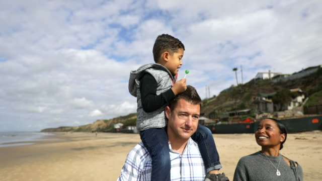 Family Walking on the Beach Piggyback Ride
