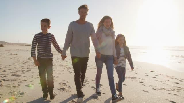 家族冬の浜辺の上を歩いて太陽のフレアと手を取り合って ビデオ