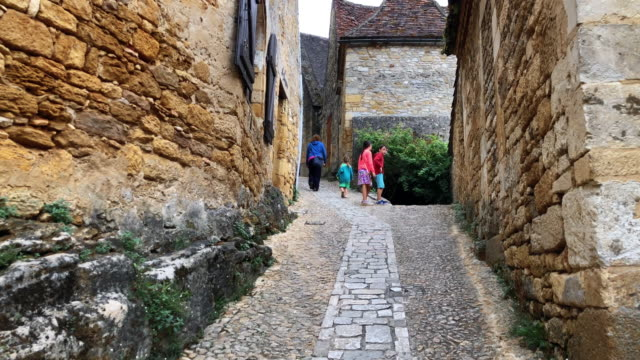 family walking through the pretty medieval cobbled streets of beynac, france - city walking background video stock e b–roll