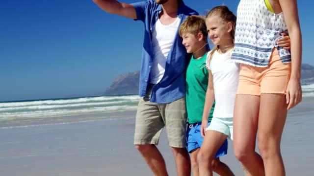 家族一緒にビーチで海岸を歩いて ビデオ