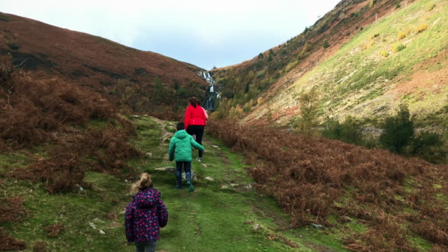 Family walking up to a Waterfall in mid Wales video