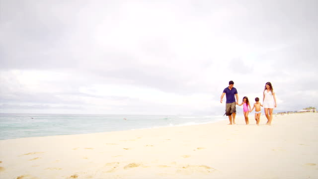 Family walks together down a beach video