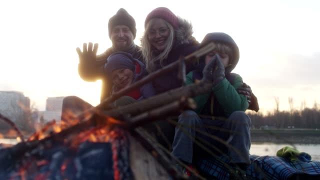 familjen värmer upp på bål. vinternöje. riverside i staden - bål utomhuseld bildbanksvideor och videomaterial från bakom kulisserna