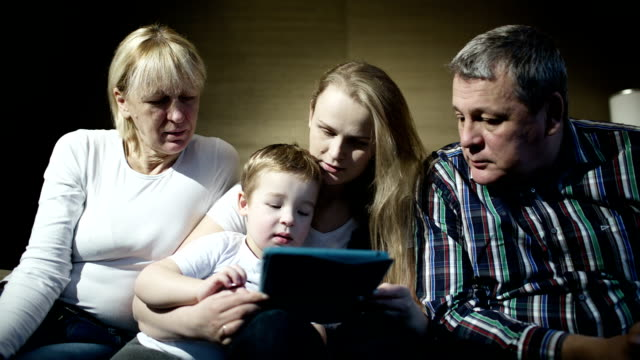Family watching boy playing game on touchpad video