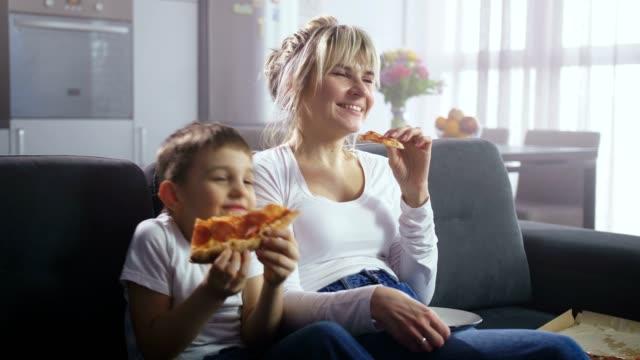 vídeos de stock e filmes b-roll de family watching comic tv show and eating pizza - tv e familia e ecrã