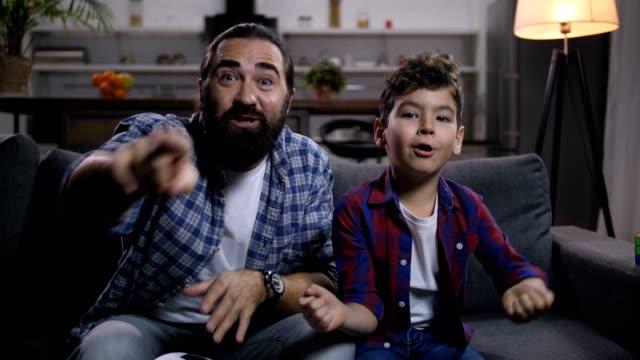 vídeos de stock e filmes b-roll de family watching football on tv rejoicing at goal - soccer supporter portrait