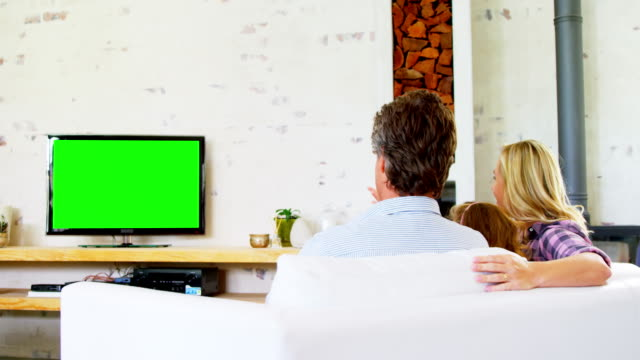 Family watching television in living room 4k Rear view of family watching television in living room at home 4k family watching tv stock videos & royalty-free footage