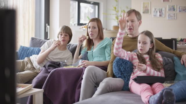 """vídeos y material grabado en eventos de stock de """"familia viendo la televisión, hablando y comiendo palomitas de maíz"""" - family watching tv"""