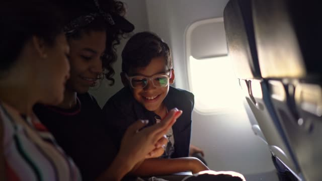 family watching video during flight - genitore unico video stock e b–roll