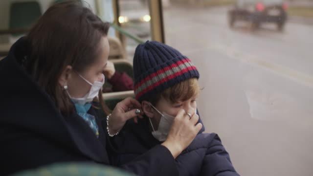 バスに保護医療マスクを着用した家族 - 警戒点の映像素材/bロール
