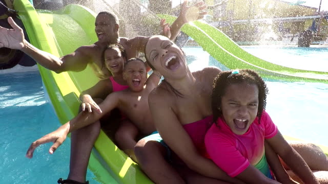 Family with 3 children waving on slide at water park video