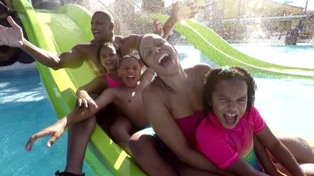 Família com 3 crianças acenando em slide no parque aquático - vídeo