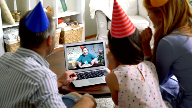 vídeos de stock e filmes b-roll de a family with a child congratulating a grandmother on her birthday using a video call. - aniversário