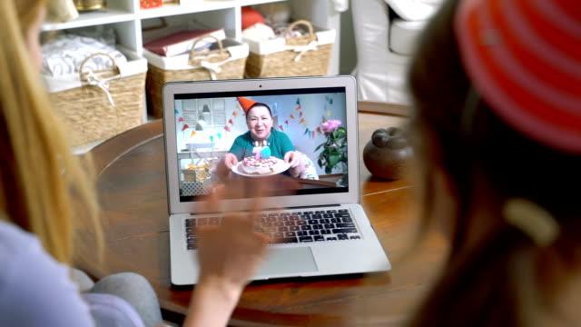 en familj med ett barn gratulera en mormor på hennes födelsedag med hjälp av ett videosamtal. - birthday celebration looking at phone children bildbanksvideor och videomaterial från bakom kulisserna