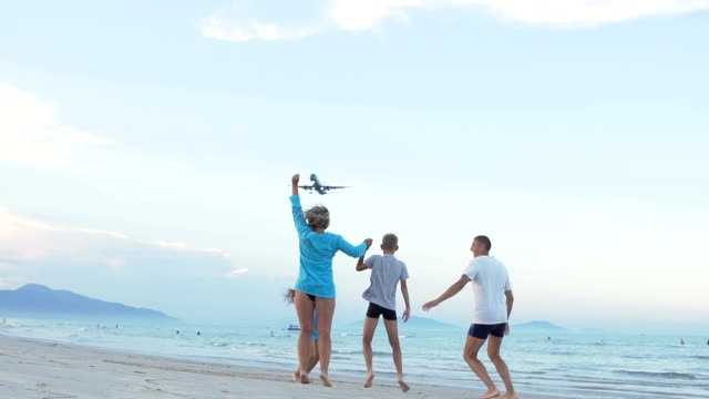 Family with a children joyfully greeting the plane landing to airport near sea. video