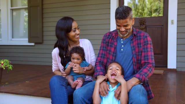 family with baby and son sit on steps of porch in front of home - portico video stock e b–roll