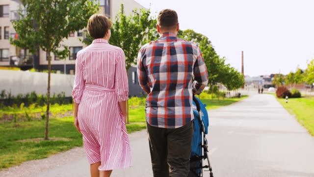 familj med baby i barnvagn gå längs staden video