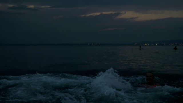Family with child bathing in sea at twilight video