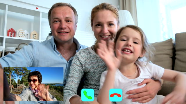 family with child chatting with grandmother using laptop video call camera - video call video stock e b–roll