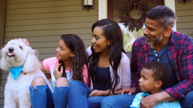 family with children and pet dog sit on steps of home - portico video stock e b–roll