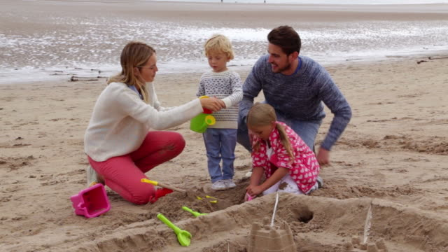 Family with children building sandcastle on beach - boy pours water from toy watering can video