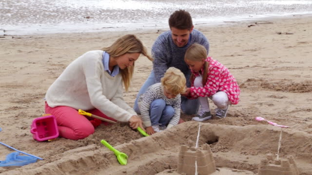 Family with children building sandcastle on beach together video