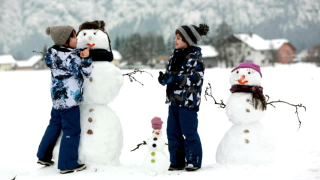 Family with children, building snowman in the park in little village in Austria, beuatiful landscape scenery. Family with children, building snowman in the park in little village in Austria, beuatiful landscape scenery. snowman stock videos & royalty-free footage