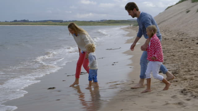 Family with children playing together by sea on beach holiday in slow motion video