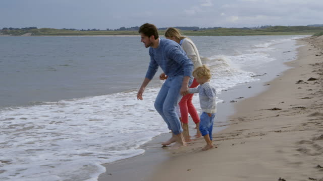 Family with children running away from waves as they break on the beach in slow motion video