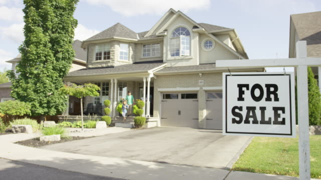 Family with 'For Sale' real estate sign video