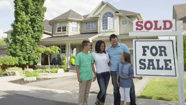"""famiglia con """"per la vendita, venduti"""" cartello di agenzia immobiliare - vendere video stock e b–roll"""