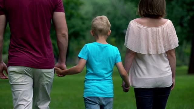 vídeos y material grabado en eventos de stock de familia con niño cogidos de la mano, pie, unión y apoyo familiar - servicios sociales