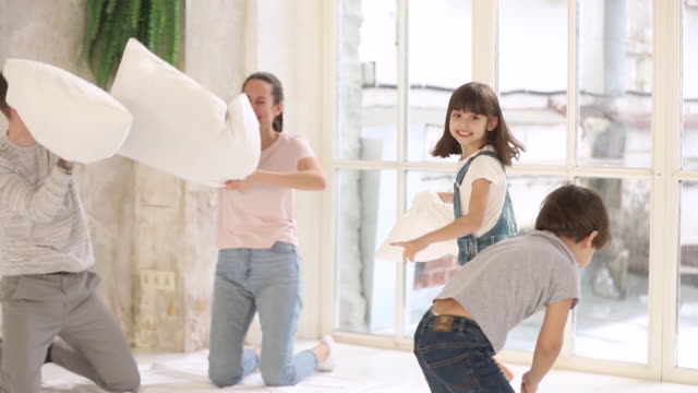 familj med små barn leker slåss med kuddar hemma - cosy pillows mother child bildbanksvideor och videomaterial från bakom kulisserna