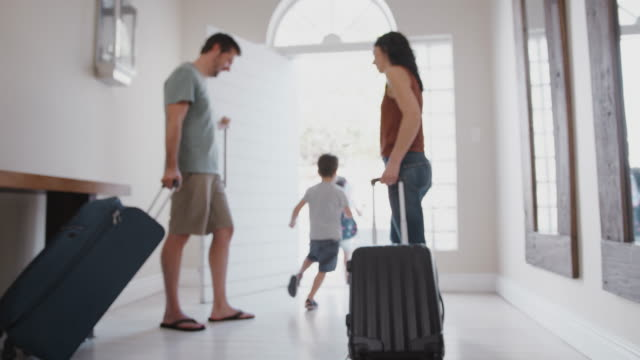 Family With Luggage Opening Front Door And Leaving For Vacation