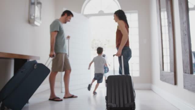 vidéos et rushes de famille avec le bagage ouvrant la porte d'entrée et partant pour des vacances - adieux