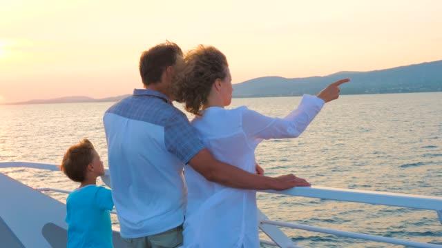 stockvideo's en b-roll-footage met gezin met één kind. hoogseizoen vakantie. kerst vakantie concept. positieve emoties. gelukkige familie reizen op zee vervoer. liefde en ondersteuning in familie. warme relaties - cruise