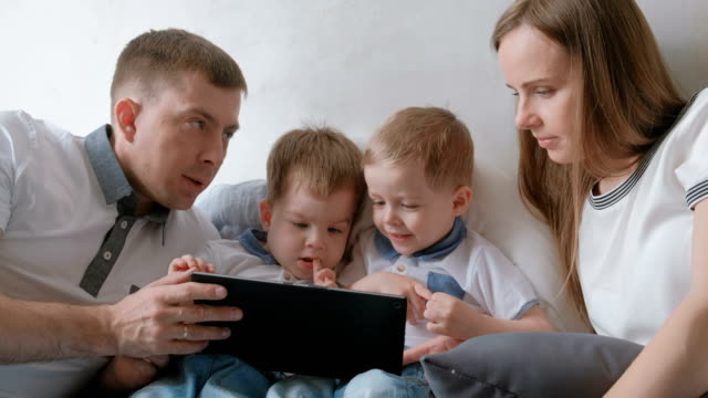 family with tablet. mom, dad and two sons twins toddlers looking cartoon at tablet lying on the bed. - gemelle video stock e b–roll
