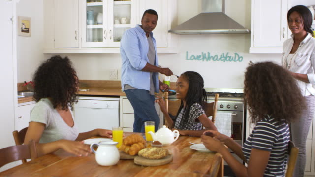 Family With Teenage Children Eating Breakfast In Kitchen video