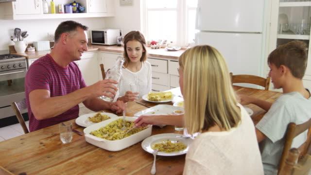 stockvideo's en b-roll-footage met gezin met tienerkinderen eten van maaltijd rond tafel in de keuken - water drinken