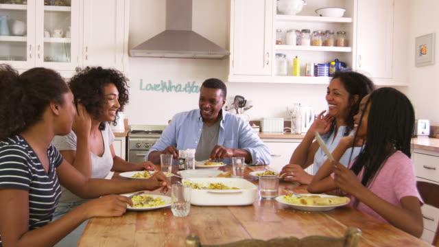 vídeos y material grabado en eventos de stock de familia con hijos adolescentes comer comida cocina - cena familiar