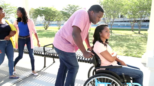 Family with teenage daughter in wheelchair An African-American family with two teenage daughters spending time outdoors together at a city park. One of the girls is in a wheelchair. Her father is pushing her and talking. Her mother and sister are walking a few steps behind them. wheelchair stock videos & royalty-free footage