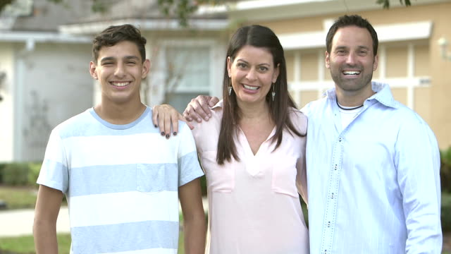 family with teenage son in front yard - couple portrait caucasian video stock e b–roll